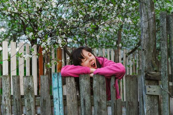 Müde Frau gähnend am Gartenzaun